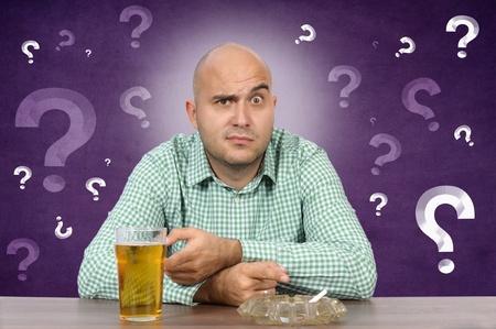 dudando: El hombre dudando si con el cigarrillo y cerveza Foto de archivo