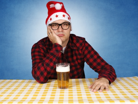 drunk party: Bored Santa with the beer. Selective focus on the man. Stock Photo