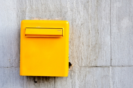 Yellow postbox on the wall photo