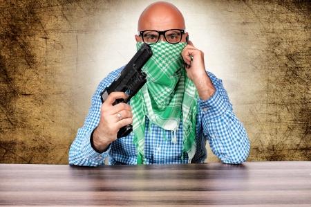 Terrorist negotiator with gun and cell phone Stock Photo - 16129218