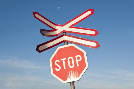 Stop and railroad signs over the blue sky photo