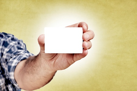 Man holding the blank white card on the yellow background Stock Photo - 16433431