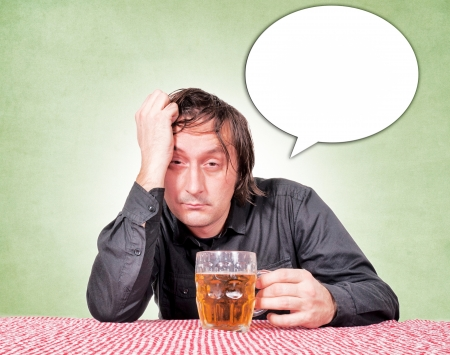 Drunk man at the pub table with a pint of beer. Stock Photo - 16844434