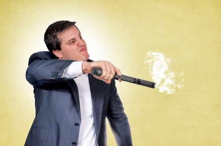 Bussinesman with the gun on yellow background Stock Photo - 16885125