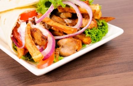 sandwiche: Portion of gyros pita on wooden table Stock Photo