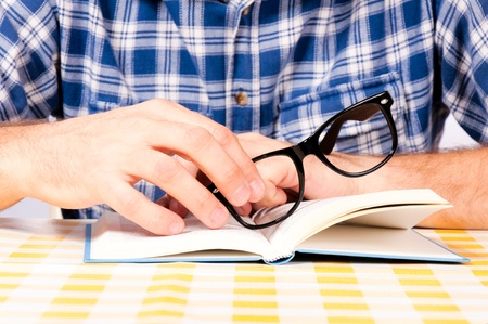 Man holding eyewear on the book Stock Photo - 17181440