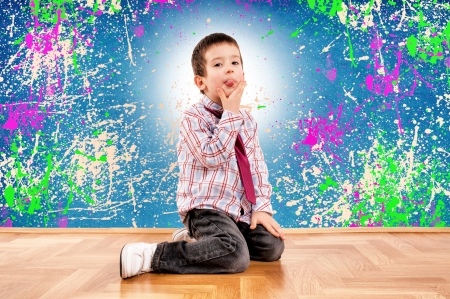 The boy sitting next to a painted wall and mocks Stock Photo - 17497727