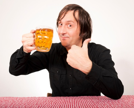 Man holding the pint of beer and showing ok sign photo