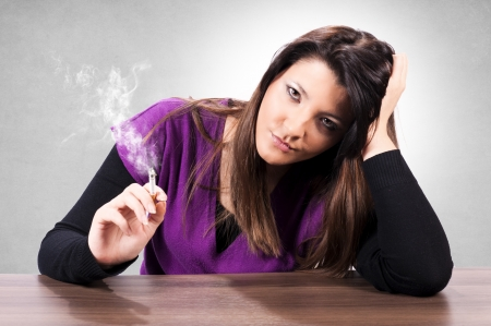 Woman smokes a cigarette with dissatisfaction photo