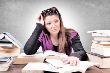 Female with contempt for learning on gray background photo