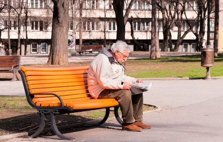 BELGRADE, SERBIA - MARCH 12 Pensioner sitting on a park bench and reading newspapers while waiting for the beginning of spring on March 12, 2013 in Belgrade, Serbia.