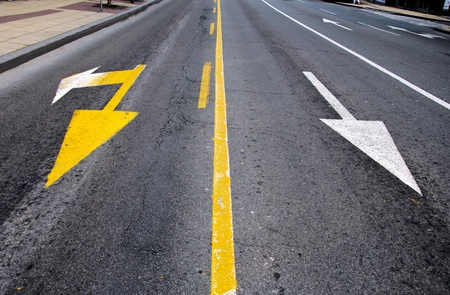 White and yellow arrows on the street photo