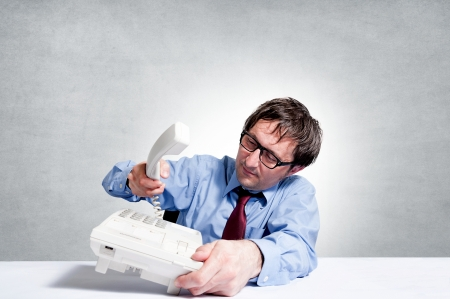 Businessman under stress breaks the handset of the phone Stock Photo - 18822008