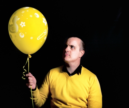 Man with yellow balloon  Shoot in low key technique Stock Photo - 18918072