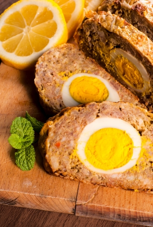 Meat and eggs roll on wooden board photo