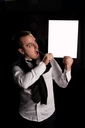 Man holding blank white board, shoot in low key. Selective focus on the white board Stock Photo - 19167721