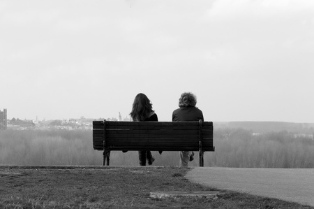 Two people sitting on bench in black and white photo