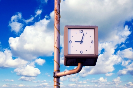 Street clock over the blue sky and white clouds photo