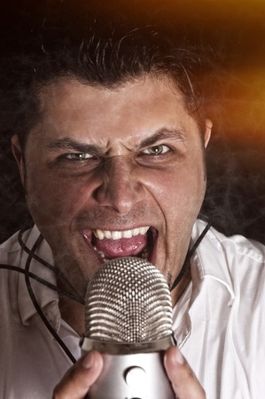 Angry singer with the mic. Selective focus on the man head photo