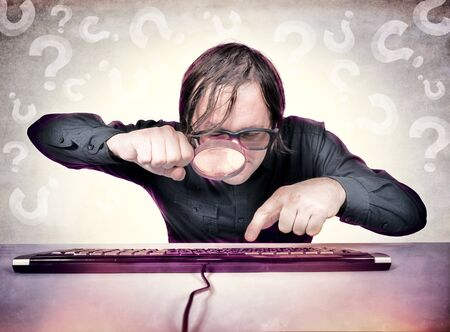 A hacker with a magnifying glass looking for something on the keyboard photo