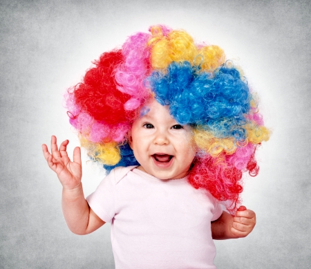 Bebé feliz con peluca de payaso Foto de archivo