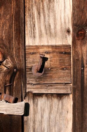 water stained: Old wooden door with metal lock