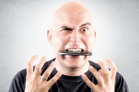 Bald guy eating mobile phone