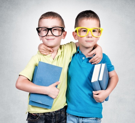 Twins holding books isolated on the gray background Stock Photo - 20568414