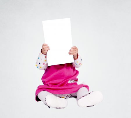 passing over: Little baby girl holding blank paper over her head Stock Photo