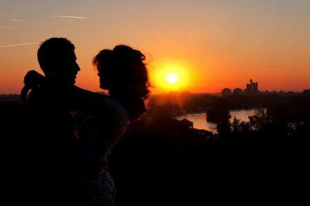 Embrace of a young couple in back light with cityscape in background Reklamní fotografie