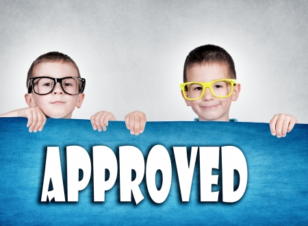 approved sign: Twins holding blank red poster with approved sign Stock Photo