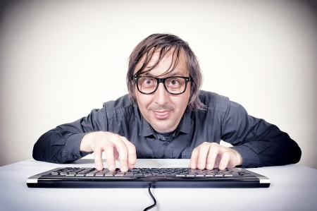 Hacker typing on the keyboard and mocking Stock Photo - 20760939