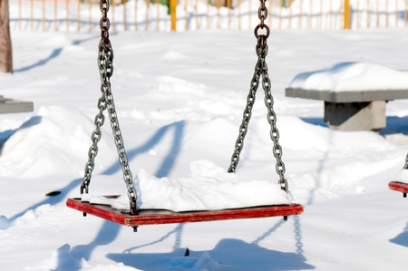 Snow on the swing in parka  photo