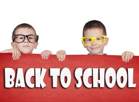 学校に戻ると空白の赤いポスターを保持している双子の署名します。 写真素材