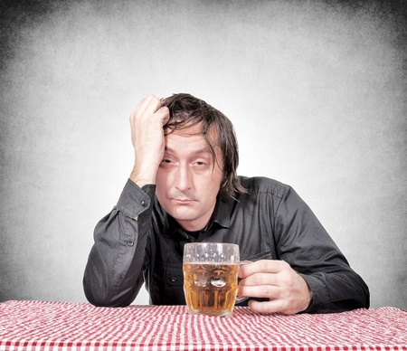 Drunk man holding the pint of beer Stock Photo - 20934338
