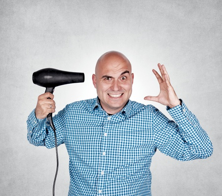 bald man: Bald guy holding hair dryer in his hand Stock Photo