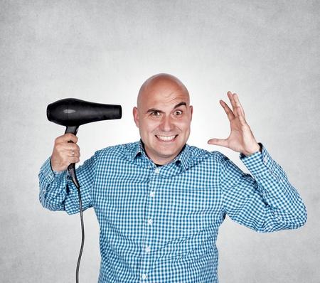 Bald guy holding hair dryer in his hand Reklamní fotografie