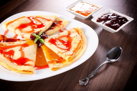 Apricot and strawberries jam on the homemade pancakes photo