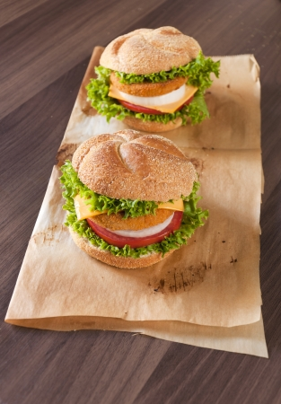 Two fish burgers on the wooden table photo