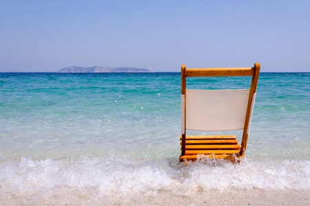 thassos: Single empty wooden chair on the beach