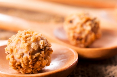 Sweet balls with chopped nuts and cream in the middle photo