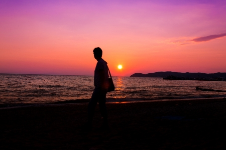 Man walking on the beach with sunset in background photo