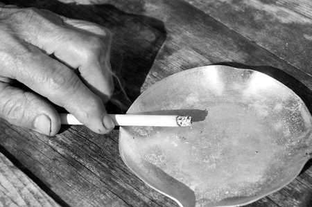Old female hand holding the cigarette.Black and white  photo