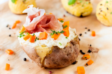 Fresh baked potato and prusciutto with white cheese cream photo