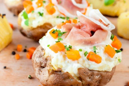 Baked and stuffed potato with vegetables and cheese cream photo
