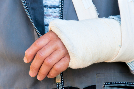 Mans arm in cast and sling photo