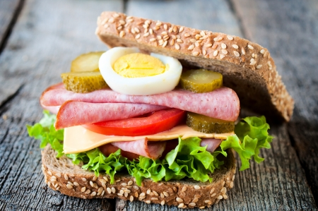 Single toast sandwich withsausage on the wooden table  photo