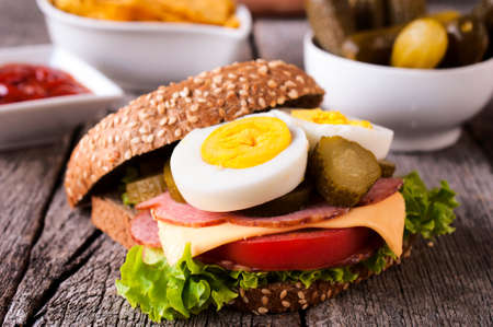Toast sandwich with vegetables,eggs,cheese and ham on wooden table photo