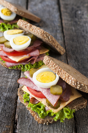 Three toast sandwiches with sausage on the table.Selective focus on the front sandwich photo