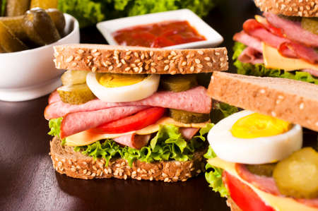 Dark bread with sausage,eggs,vegetables and cheese.Selective focus on sandwich in the middle  photo